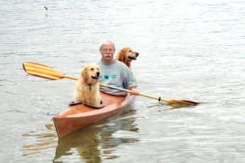 Мужчина и две собаки в лодке